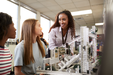 Woman Teacher With Female College Students Building Machine In Science Robotics Or Engineering Class 写真素材