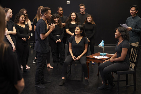 Profesor con estudiantes masculinos y femeninos de drama en la escuela de artes escénicas en clase de improvisación de estudio