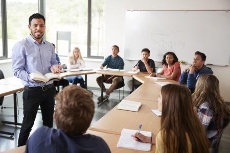 Male High School Tutor With Pupils Sitting At Table Teaching Maths Class 版權商用圖片