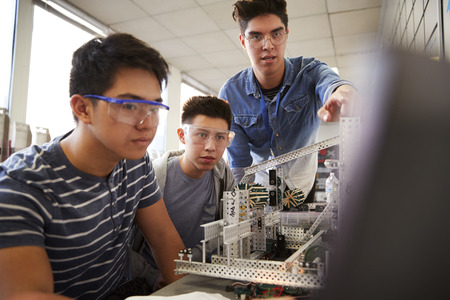 Teacher With Two Male College Students Building Machine In Science Robotics Or Engineering Class Stock Photo
