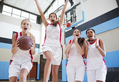 Portrait Of Female High School Basketball Team Celebrating On Court 写真素材