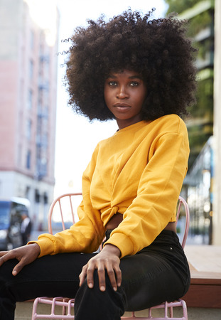Young black woman with afro hair and sitting on a chair in the street looking to camera, vertical Фото со стока