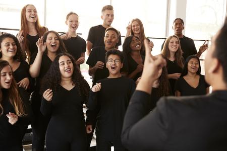 Mannelijke en vrouwelijke studenten zingen in koor met leraar aan de kunstacademie Perform