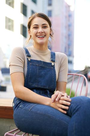 Jeune femme hispanique à la mode portant une salopette assise dans la rue en riant à la caméra, gros plan