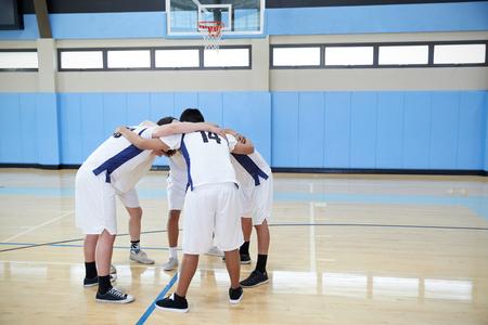Les joueurs de basket-ball de lycée masculins dans Huddle ayant des discussions d'équipe sur le terrain Banque d'images