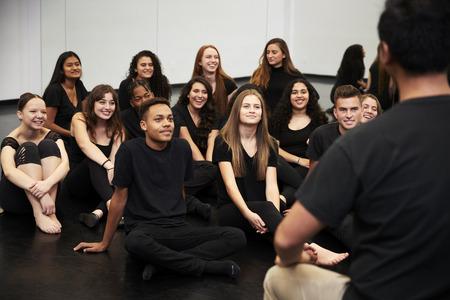 리허설 스튜디오에서 바닥에 앉아있는 학생들과 이야기하는 공연 예술 학교의 교사 스톡 콘텐츠