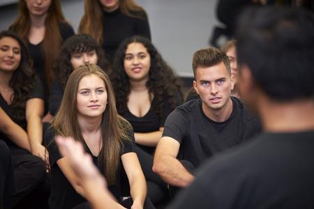 Teacher At Performing Arts School Talking To Students Sitting On Floor In Rehearsal Studio Stock fotó