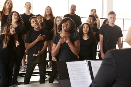 Männliche und weibliche Schüler singen im Chor mit Lehrer an der Performing Arts School