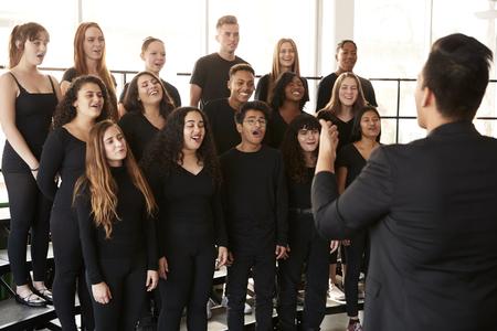 Estudiantes masculinos y femeninos cantando en coro con el maestro en la escuela de artes escénicas