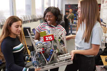 Female University Students Carrying Machine In Science Robotics Or Engineering Class