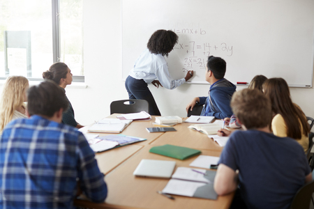 Female High School Tutor At Whiteboard Teaching Maths Class Stock Photo