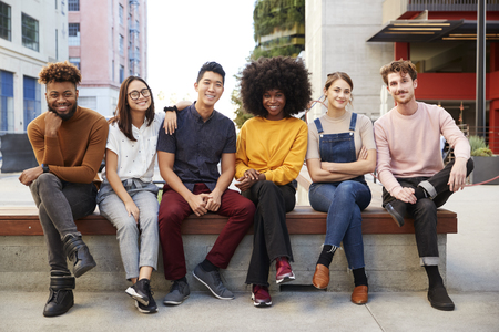 Six young adult friends sitting in a row on a bench in a city street smiling to camera, full length