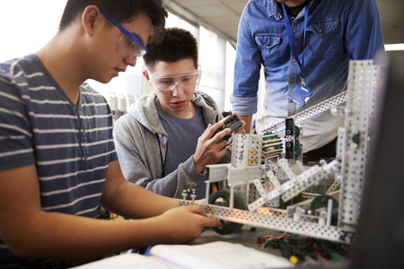 Teacher With Two Male College Students Building Machine In Science Robotics Or Engineering Class 免版税图像