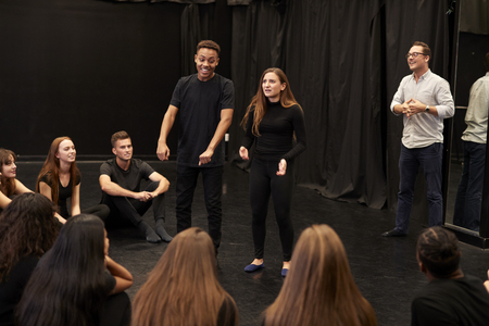 Teacher With Male And Female Drama Students At Performing Arts School In Studio Improvisation Class 스톡 콘텐츠