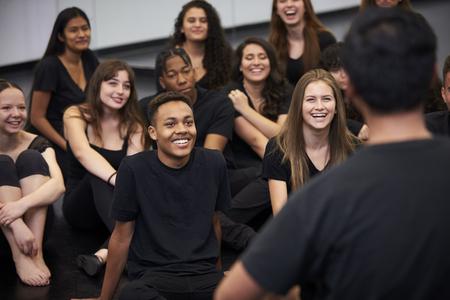 Profesor en la escuela de artes escénicas hablando con estudiantes sentados en el piso en el estudio de ensayo
