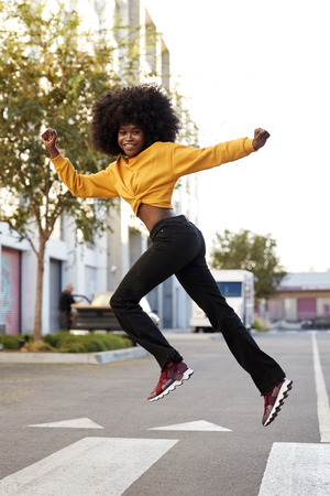 Young black woman with afro jumps, looking to camera, while crossing street, side view, vertical