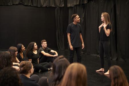 Estudiantes masculinos y femeninos de drama en la escuela de artes escénicas en clase de improvisación de estudio