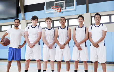 Portrait Of Male High School Basketball Team With Coach On Court Stock Photo