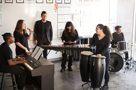 Students At Performing Arts School Playing In Band At Rehearsal With Teacher Stock Photo
