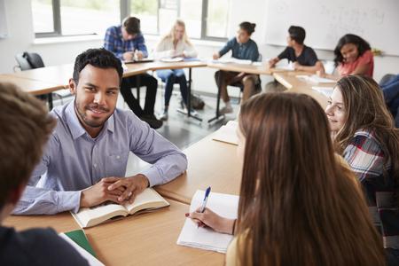 Male High School Tutor With Pupils Sitting At Table Teaching Maths Class 免版税图像