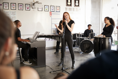 Students At Performing Arts School Playing In Band At Rehearsal Imagens