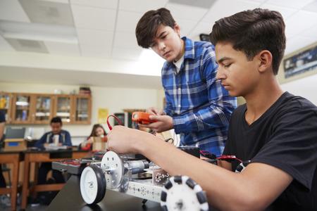 Dos alumnos varones construcción de vehículos robóticos en la lección de ciencias