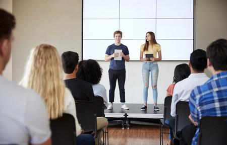 Estudiantes con tabletas digitales dando una presentación a la clase de la escuela secundaria frente a la pantalla Foto de archivo