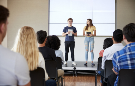 Students With Digital Tablets Giving Presentation To High School Class In Front Of Screen