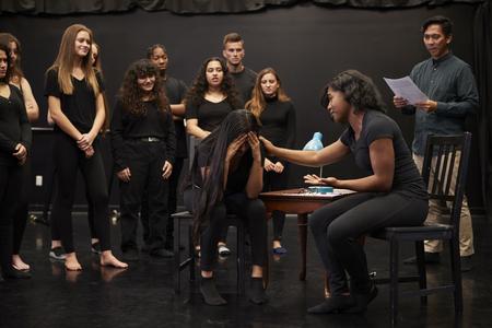 Profesor con estudiantes masculinos y femeninos de drama en la escuela de artes escénicas en clase de improvisación de estudio Foto de archivo