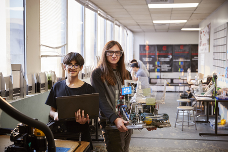 Portrait Of Male College Students With Computer Controlled Rig In Science Or Robotics Class