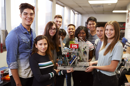 Portrait Of University Students With Teacher Holding Machine In Science Or Robotics Class