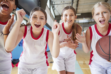 Portrait Of Female High School Basketball Team Celebrating On Court Imagens
