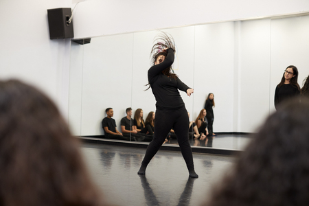 Female Student At Performing Arts School Performs Street Dance For Class And Teacher In Dance Studio Imagens