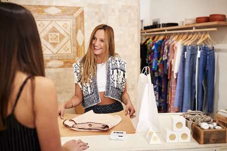 Sales Assistant Serving Female Customer In Independent Clothing Or Gift Store Imagens