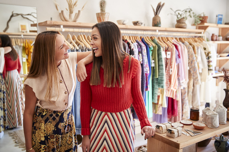 Two Female Sales Assistants Working In Independent Clothing And Gift Store
