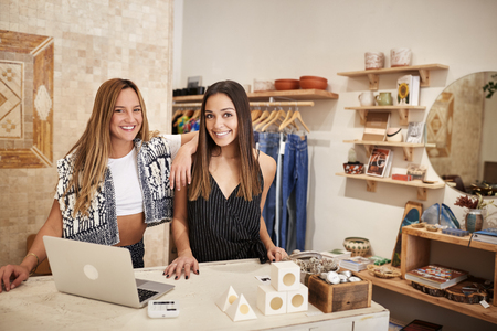 Portrait Of Two Female Owners Of Independent Clothing And Gift Store Behind Sales Desk