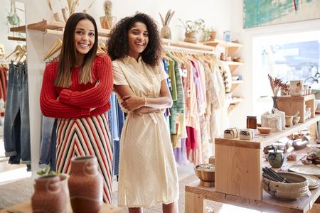 Portret van twee vrouwelijke verkoopassistenten die in een kleding- en cadeauwinkel werken