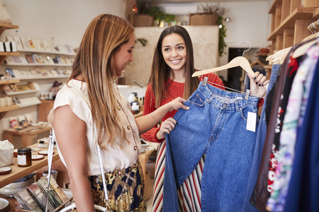 Two Female Friends Shopping In Independent Clothing Store Looking At Racks Imagens