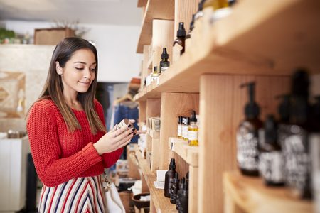 Female Customer Shopping In Independent Cosmetics Store Comparing Prices Using Mobile Phone