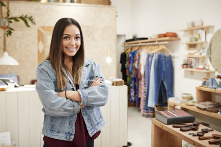 Portrait Of Female Owner Of Independent Clothing And Gift Store Standing By Sales Desk Imagens