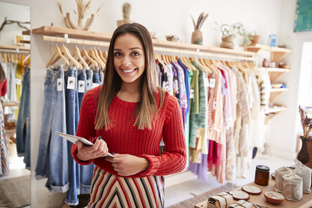 Portret właścicielki niezależnego sklepu z odzieżą i upominkami z cyfrowym tabletem