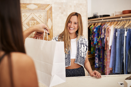 Sales Assistant Serving Female Customer In Independent Clothing Or Gift Store 写真素材