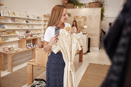 Female Customer Shopping In Independent Fashion Store Using Mobile Phone To Take Picture Of Dress Imagens