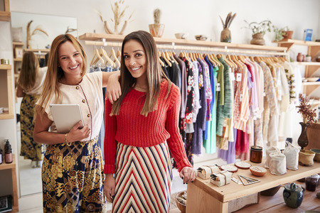 Portrait Of Two Female Sales Assistants With Digital Tablet Working In Clothing And Gift Store
