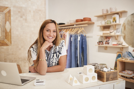 Portrait Of Female Owner Of Independent Clothing And Gift Store Behind Sales Desk