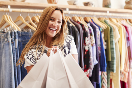 Portrait Of Female Customer Standing By Racks Of Clothes In Independent Fashion Store Holding Bags