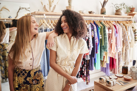Two Female Sales Assistants Working In Clothing And Gift Store Imagens