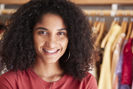 Portrait Of Female Customer Or Owner Standing By Racks Of Clothes In Independent Fashion Store Imagens