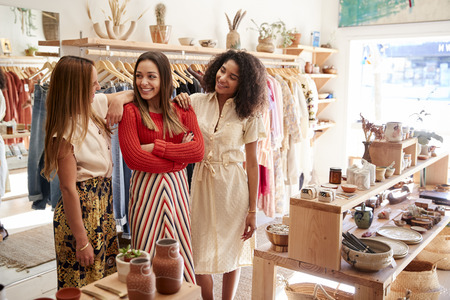 Three Female Sales Assistants Working In Clothing And Gift Store