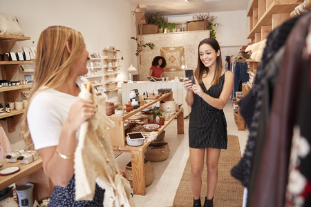 Friends Taking Photos On Mobile Phone As They Choose Dresses In Independent Fashion Store Imagens